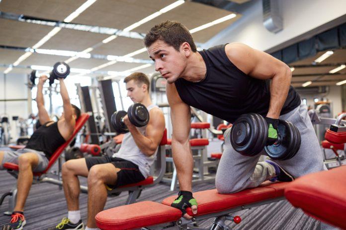 Новичок в тренажерном зале выполняет упражнение: тяга гантели одной рукой в наклоне