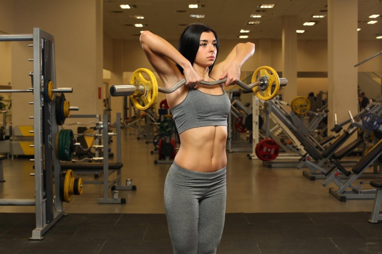 Упражнение в исполнении девушки: тяга штанги к подбородку