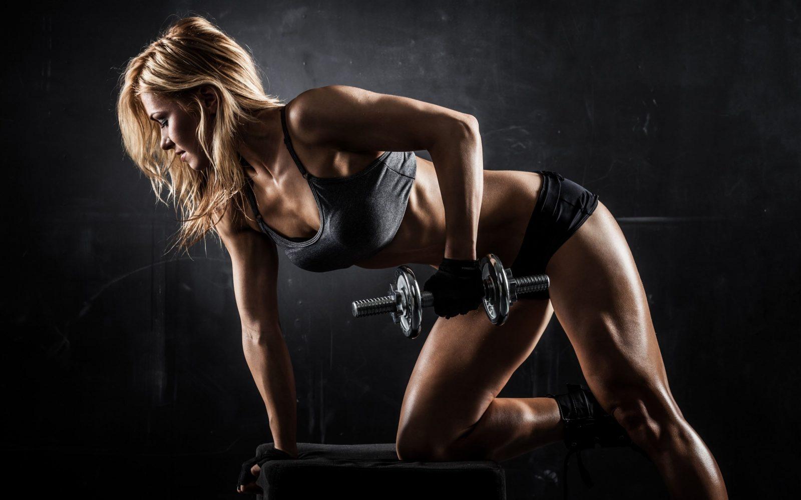 Девушка выполняет упражнение тяга гантели одной рукой в наклоне на скамье