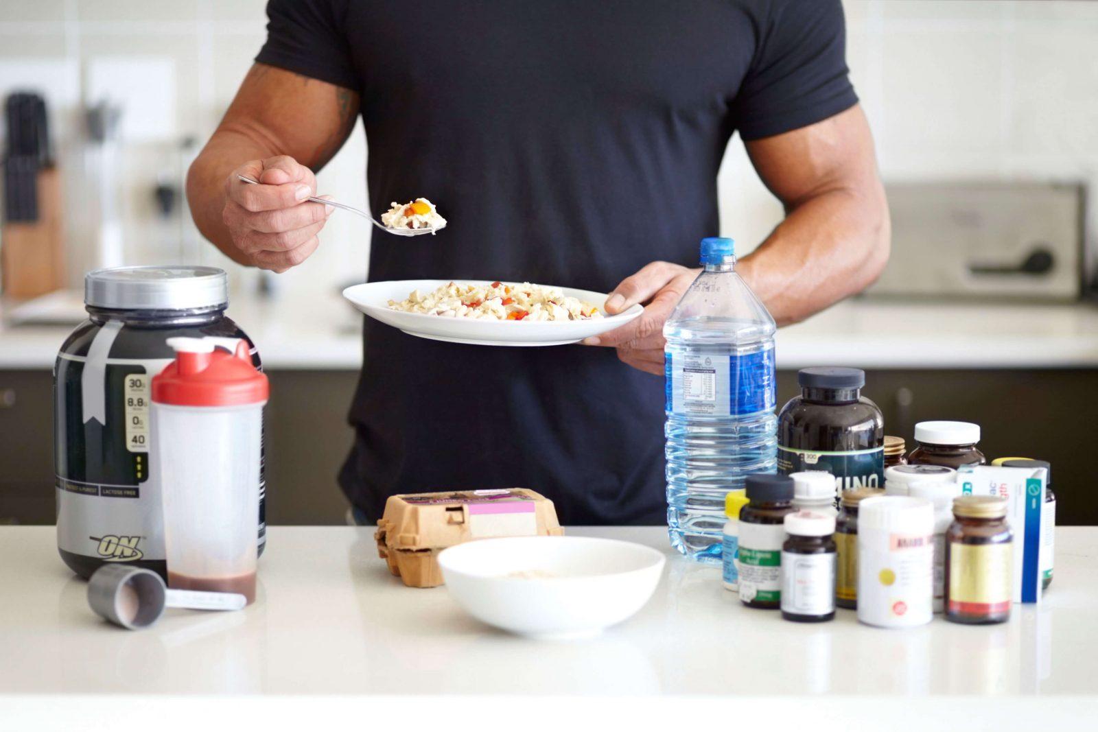 Накаченный атлет, шейкер с протеином, бутылка воды, салат