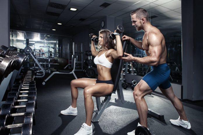 Атлетичный парень страхует спортивную девушку в тренажерном зале