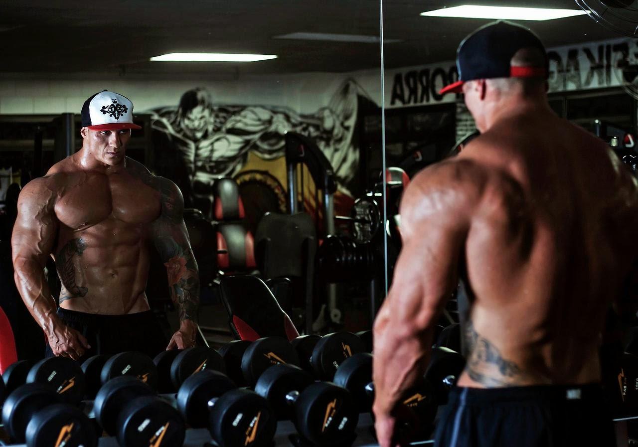 Накаченный атлет в кепке с голым торсом смотрит в зеркало