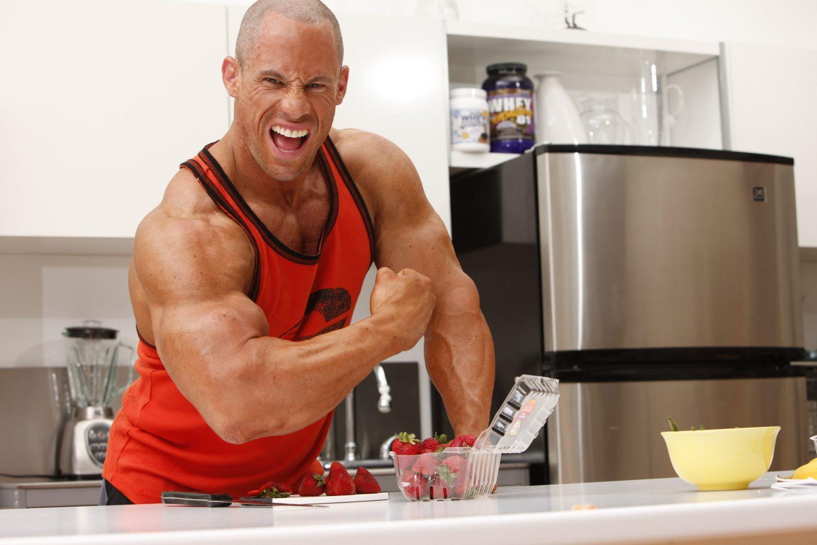 Атлет на кухне в красной майке демонстрирует объем бицепса