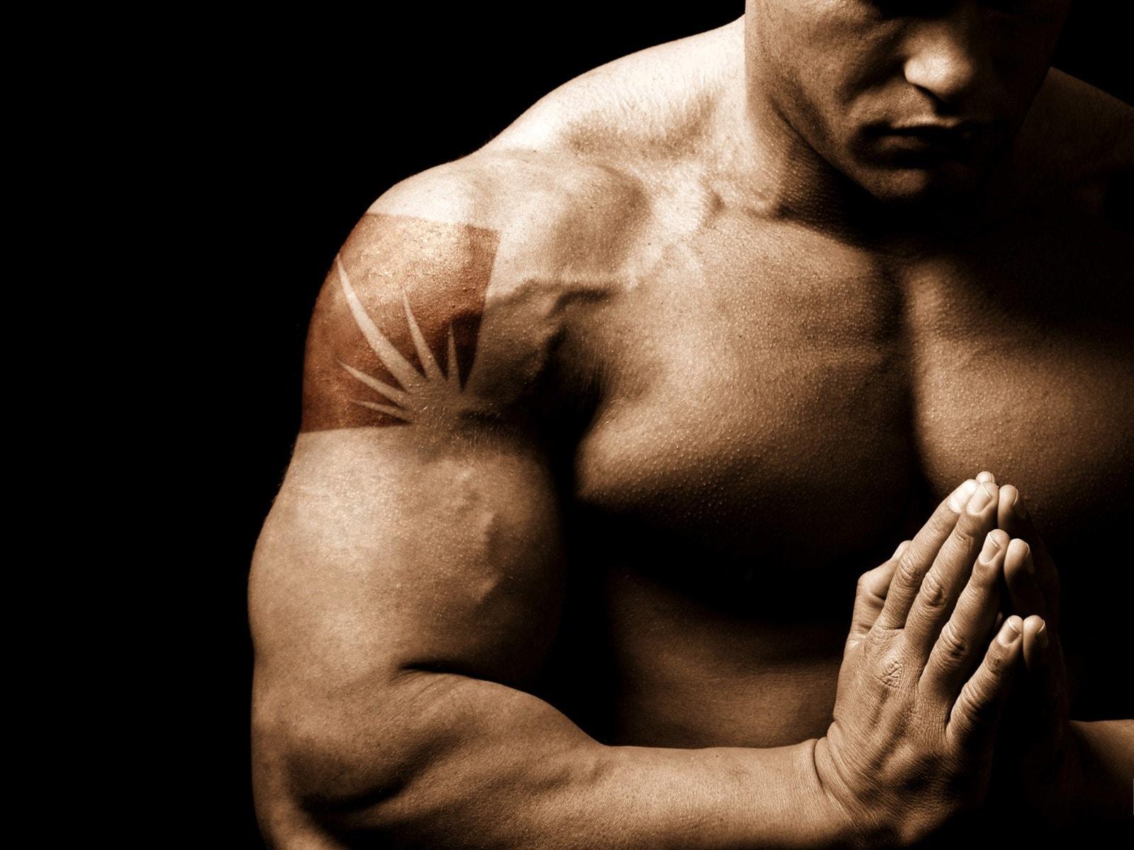 Накаченный атлет с татуировкой медитирует на черном фоне