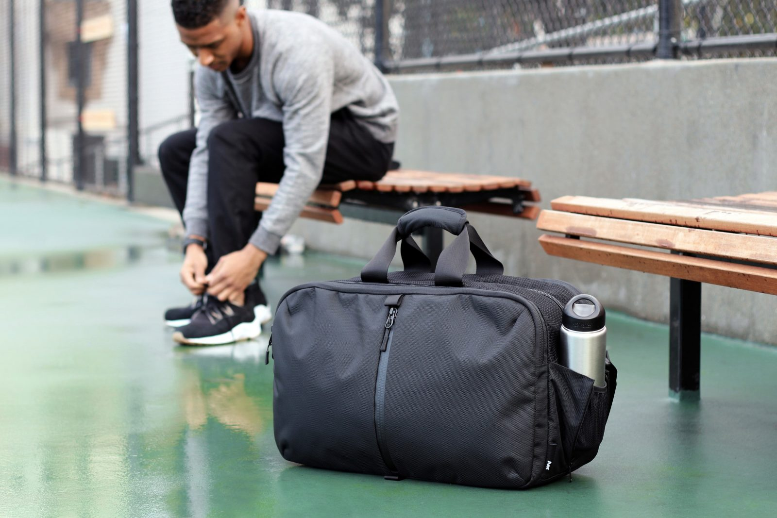 Спортивная сумка на фоне атлета, который завязывает шнурки, сидя на лавочке