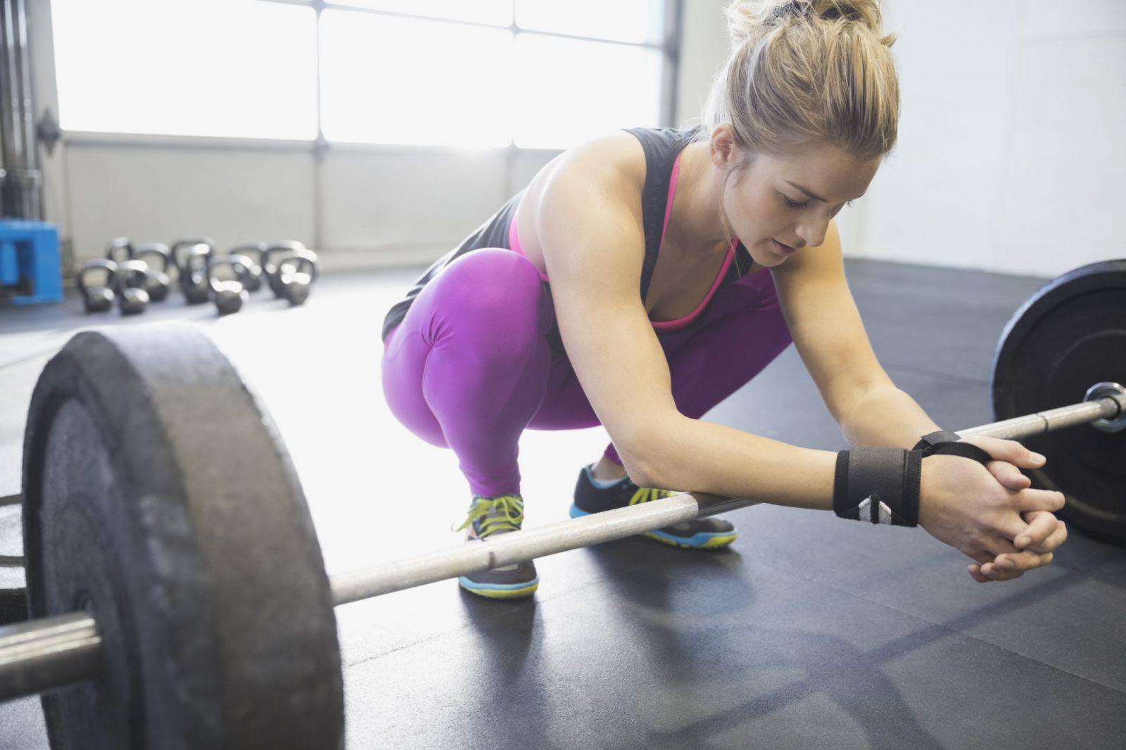 Спортивная девушка присела на корточки облокотившись руками на штангу