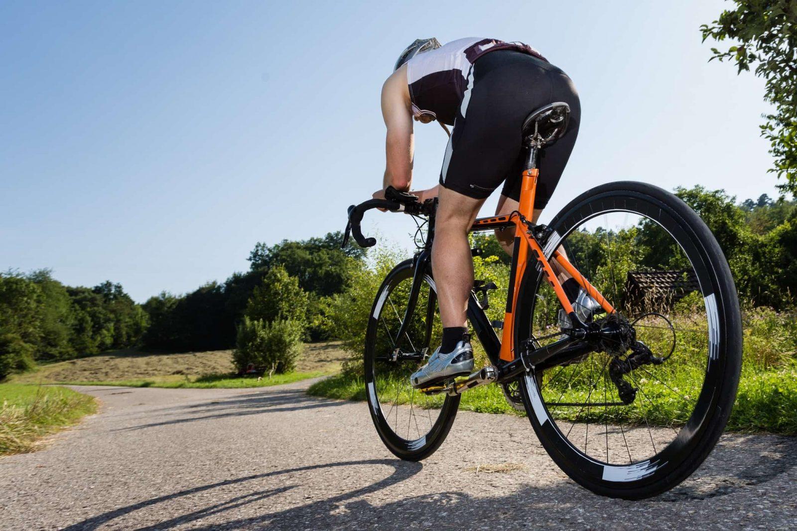 Профессиональный спортсмен проезжает в лесополосе на велосипеде