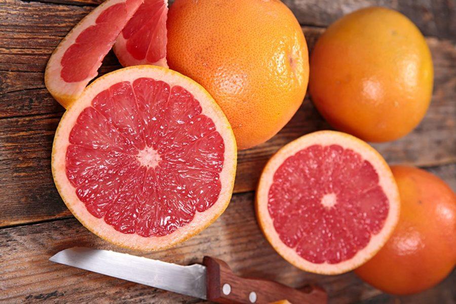 Грейпфрут (ломтики) на деревянном фоне