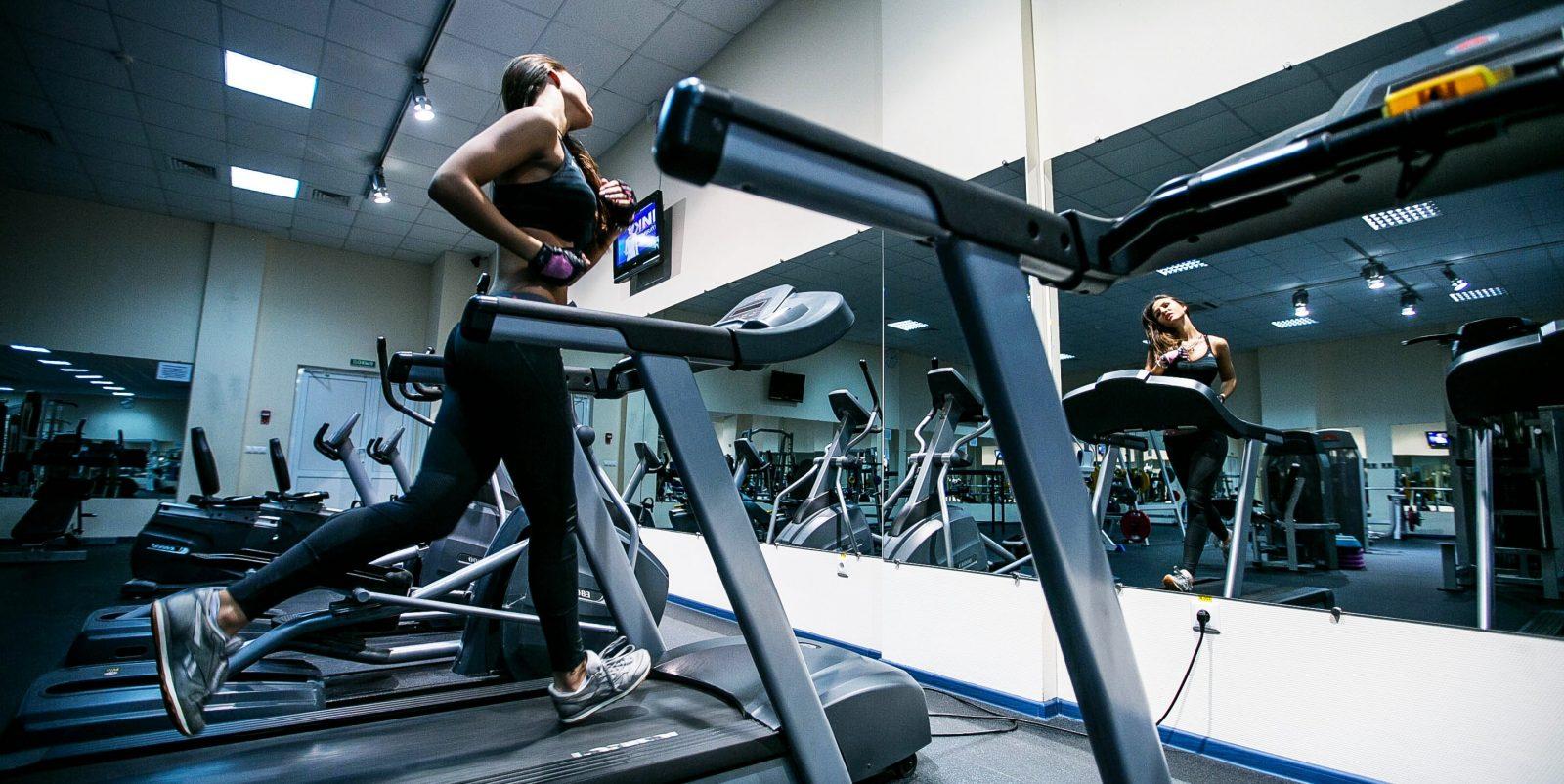 Спортивная девушка выполняет пробежку в тренажерном зале
