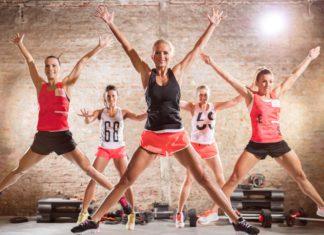 Мужчины и женщины расставив ноги и руки в стороны активно занимаются спортом