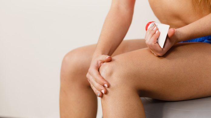 Девушка мажет коленный сустав мазью