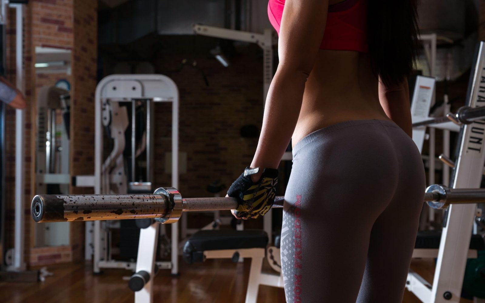 Девушка со штангой в тренажерном зале