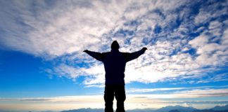 Человек раскинув руки устремляет свой взгляд на небо голубое