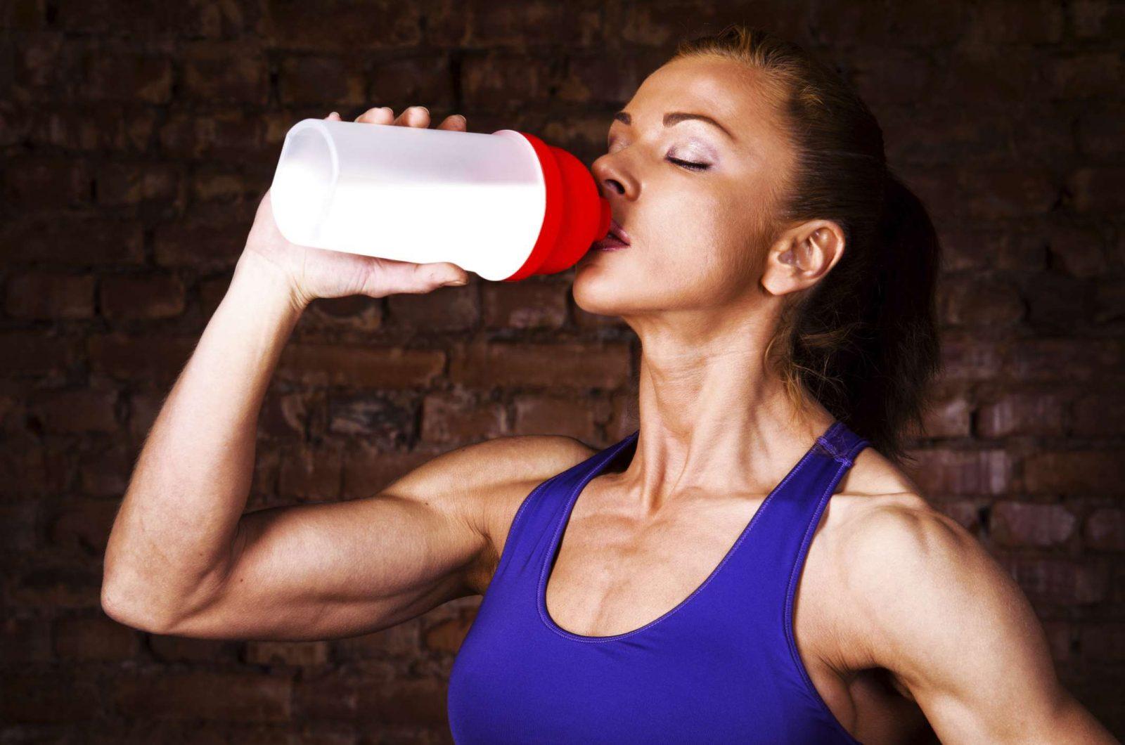 Девушка пьет протеиновый напиток из шейкера