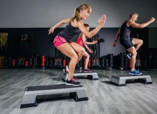 Мужчины и женщины выполняют аэробное упражнение