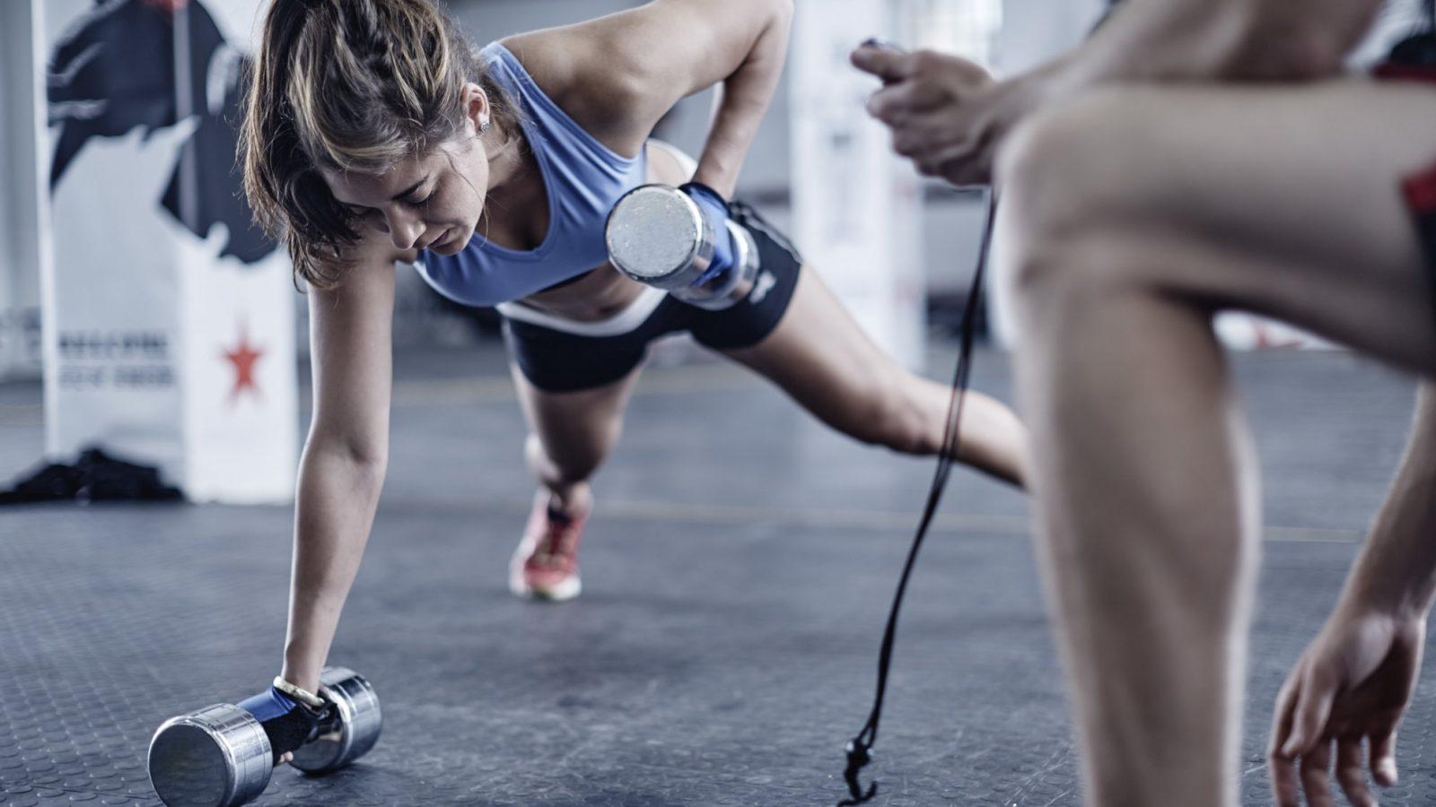 Спортивная девушка отжимается от пола с гантелями в руках
