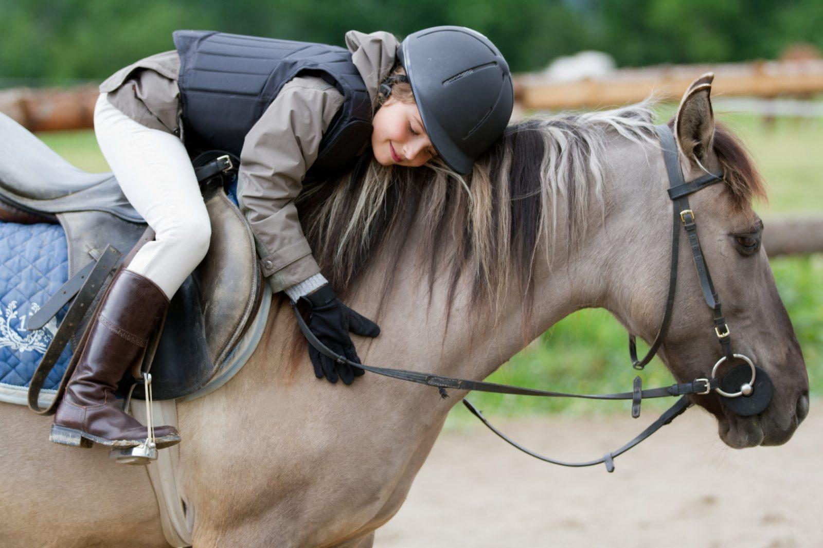 Ребенок занимается спортивной ездой на лошади