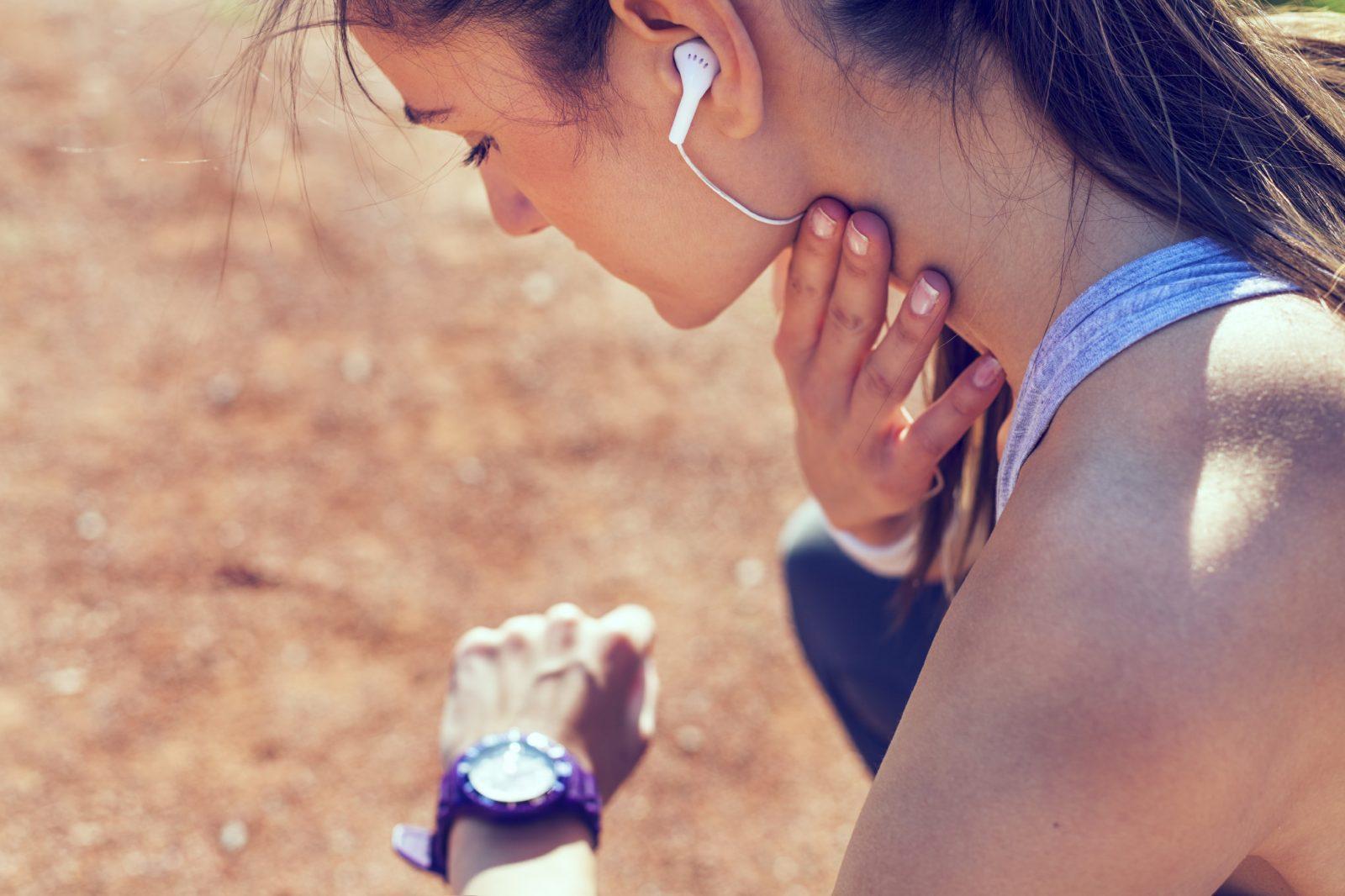 Спортивная девушка в наушниках измеряет пульс рукой возле шеи, смотря на ручные часы