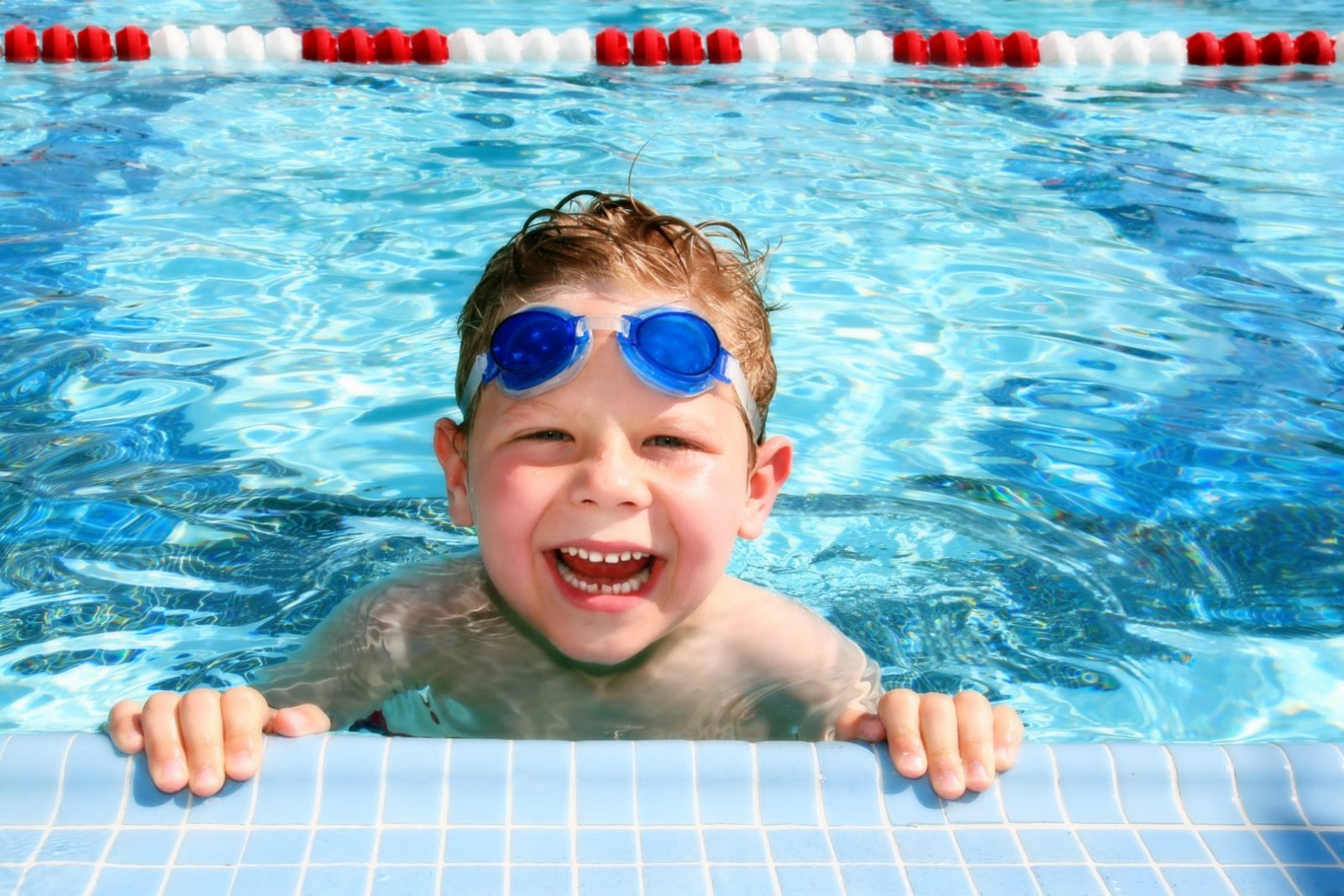 Маленький ребенок в плавательных очках в бассейне