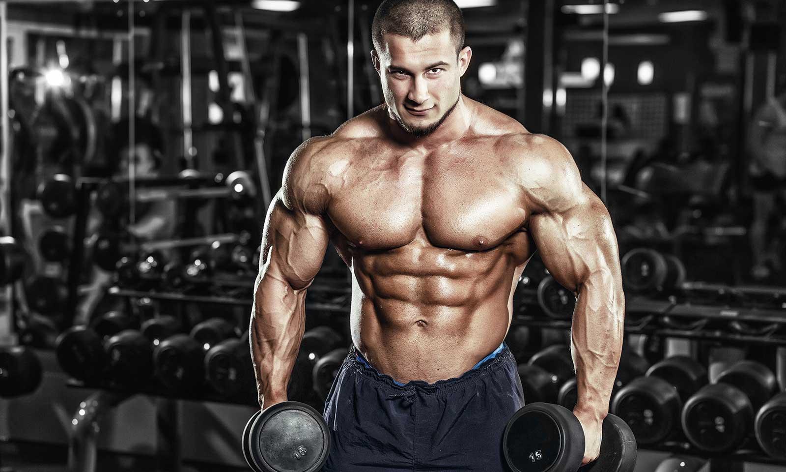 Накаченный атлет с голым торсом и гантелями в руках, демонстрирует в тренажерном зале рельефные мышцы