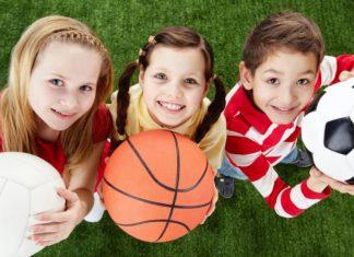 Три девочки сразными мячами спортивными: волейбольным, футбольным и баскетбольным