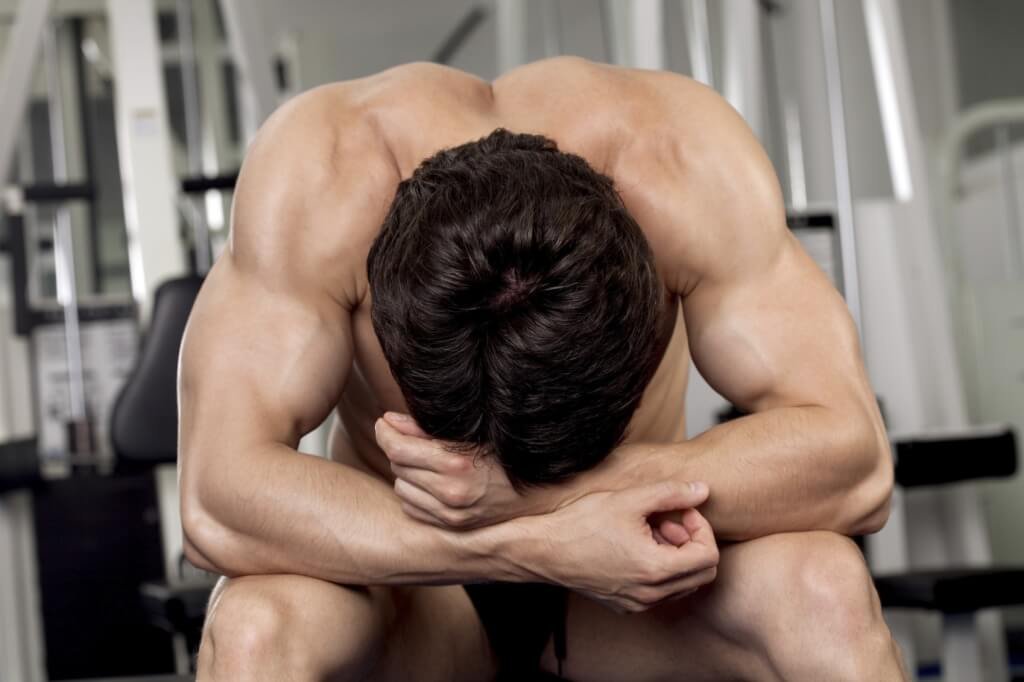 Спортивный парень с голым торсом в тренажерном зале сидя опустил низко голову