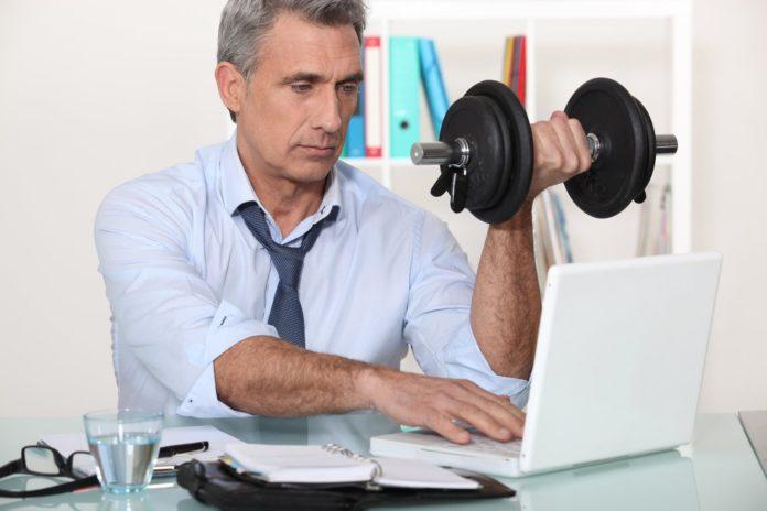 Мужчина в белой рубашки и галстуке на рабочем месте поднимает гантель