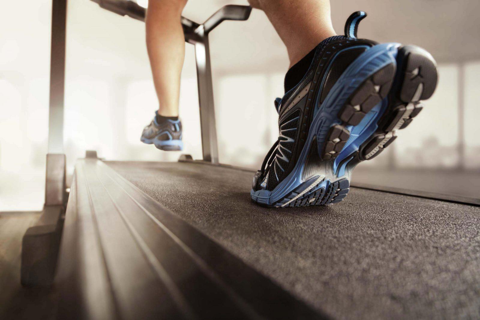 Парень в кроссовках бежит по беговой дорожке в спортзале