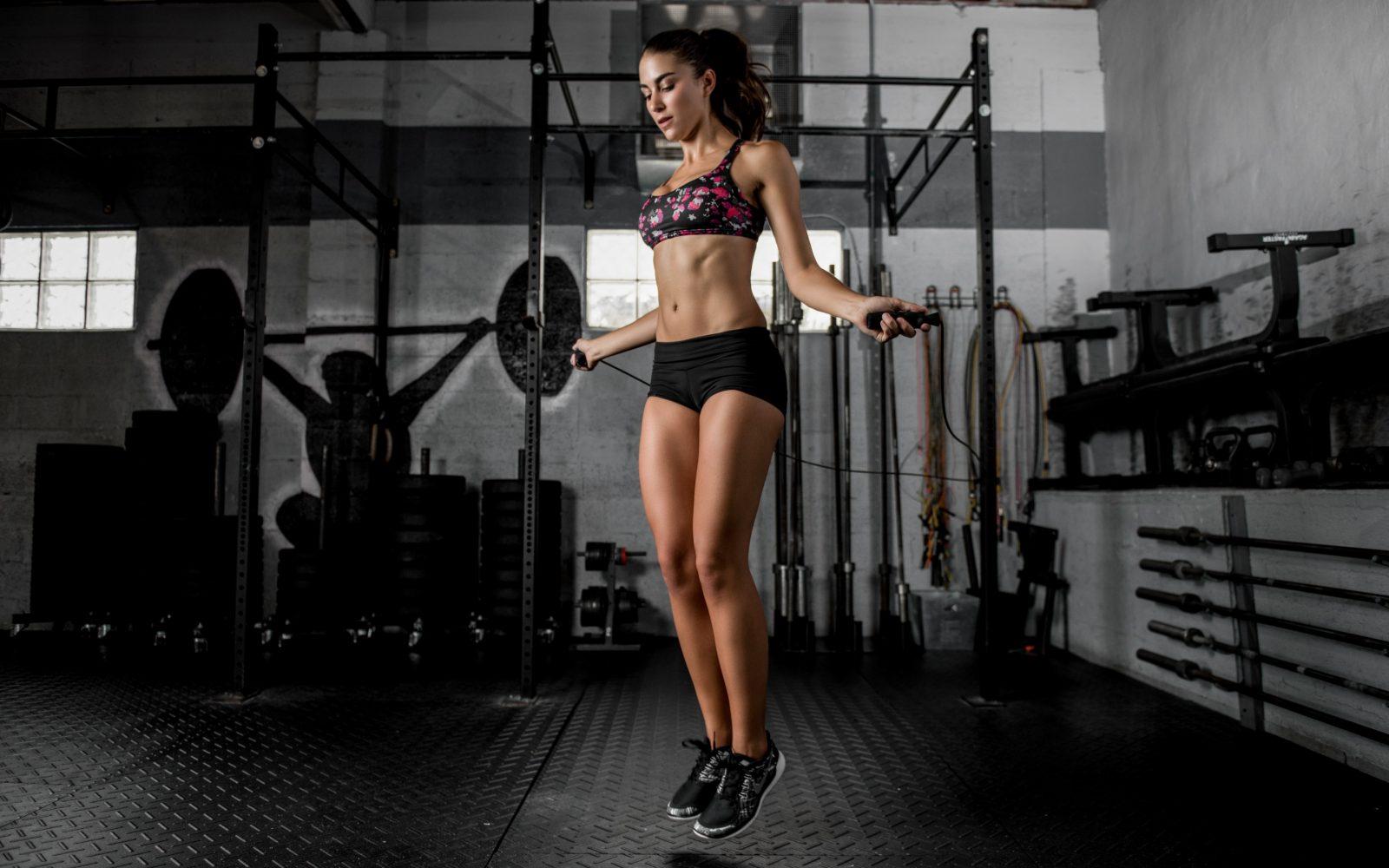 Аэробная тренировка в тренажерном зале: девушка прыгает на скакалке