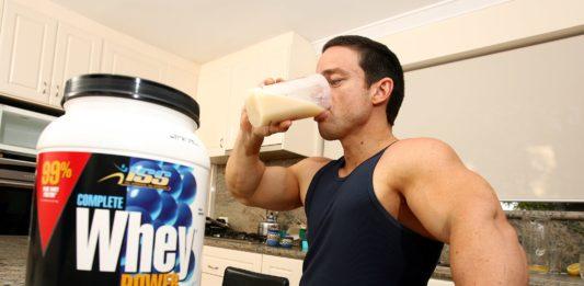 Накаченный атлет пьет из шейкера пьет сывороточный протеин