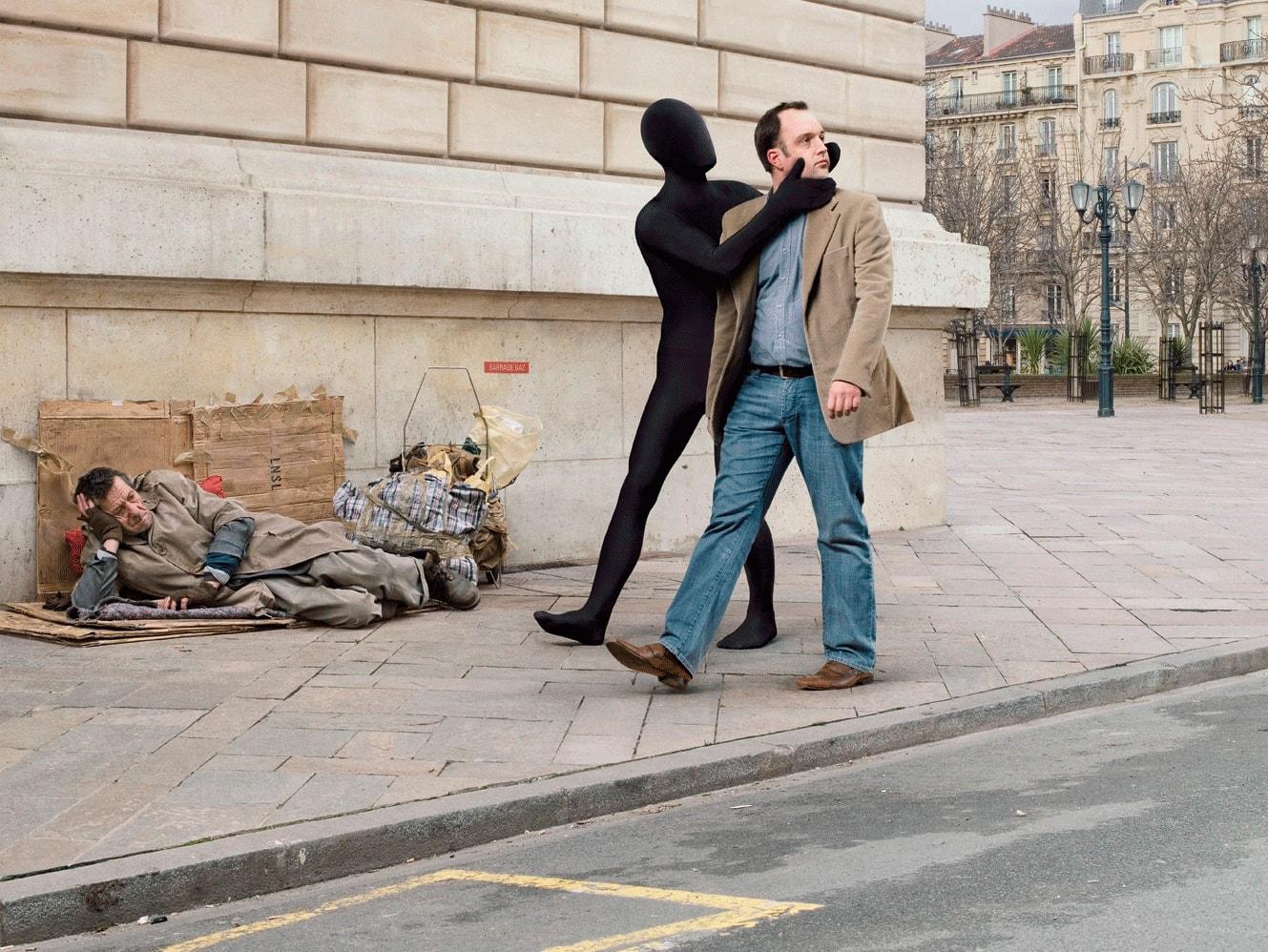 Мужчина отвернувшись равнодушно проходит мимо бездомного