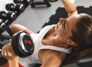 Спортивная девушка выполняет жимы гантелей на наклонной скамье в тренажерном зале