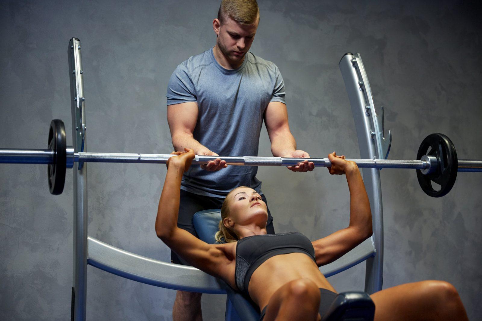 Парень подстраховывает девушку в упражнении - жим штанги на наклонной скамье