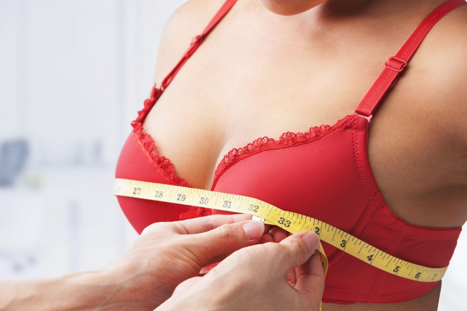 Девушке в красном бюстгальтере измеряют сантиметровой лентой грудь
