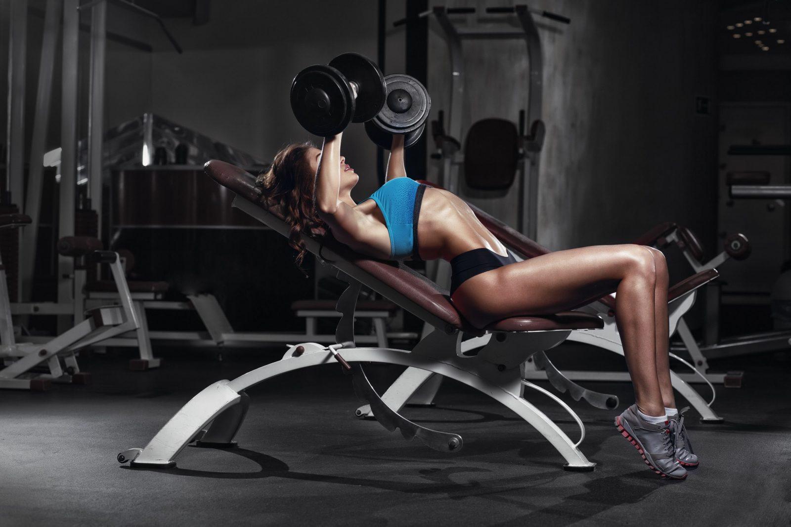 Девушка выполняет жим гантелей на наклонной скамье в тренажерном зале