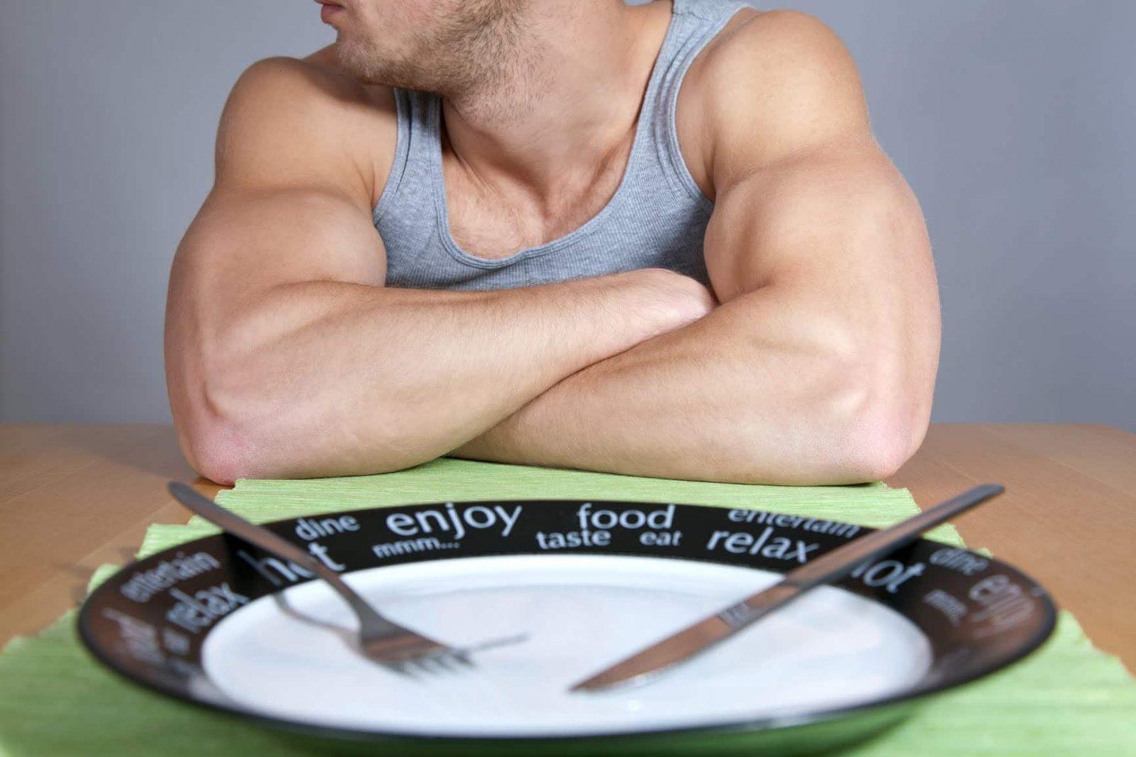 Атлет сидит за столом, на котором стоит пустая тарелка с ножом и вилкой
