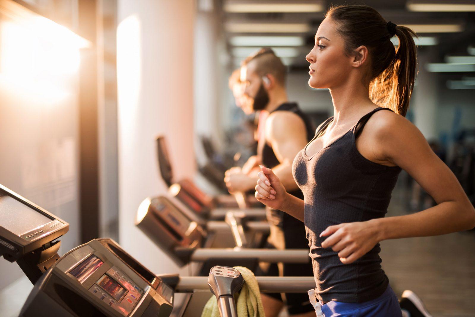 Парни и девушки выполняют пробежку на беговой дорожке в тренажерном зале