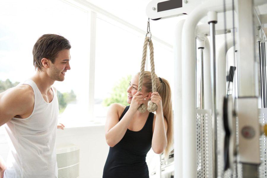 Девушка мило беседует с парнем в тренажерном зале во время выполнения упражнения
