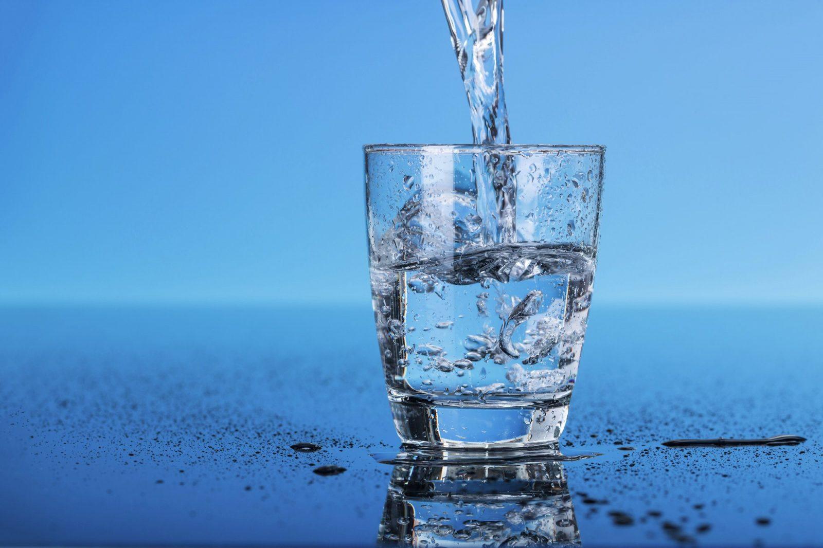 Прозрачный стакан на голубом фоне, в который заливают чистую воду