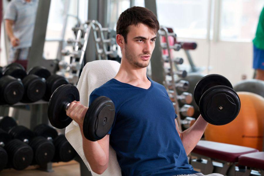 Начинающий худой атлет, выполняет одновременный подъем гантель на бицепс