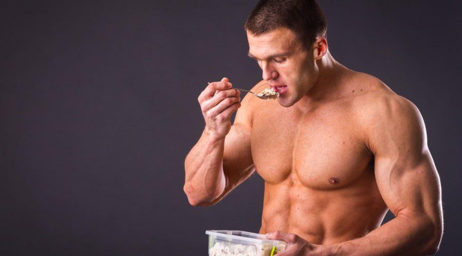 Подкаченный спортсмен кушает ложкой из пищевого контейнера сложные углеводы и белки