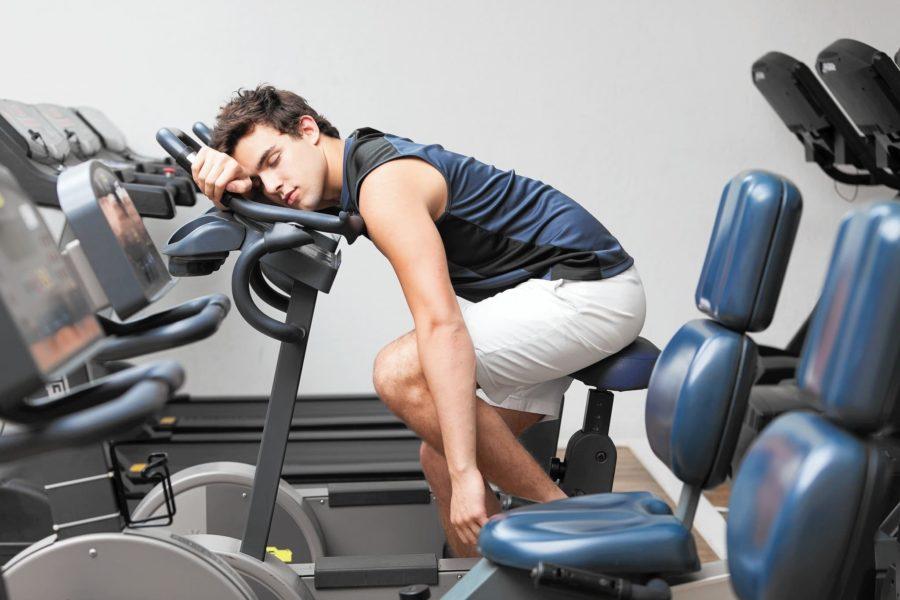 Уставший (сонный) атлет на велотренажере