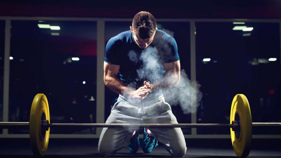 Спортсмен настраивается на рабочий подход перед штангой хлопнув в ладоши смазанные магнезией
