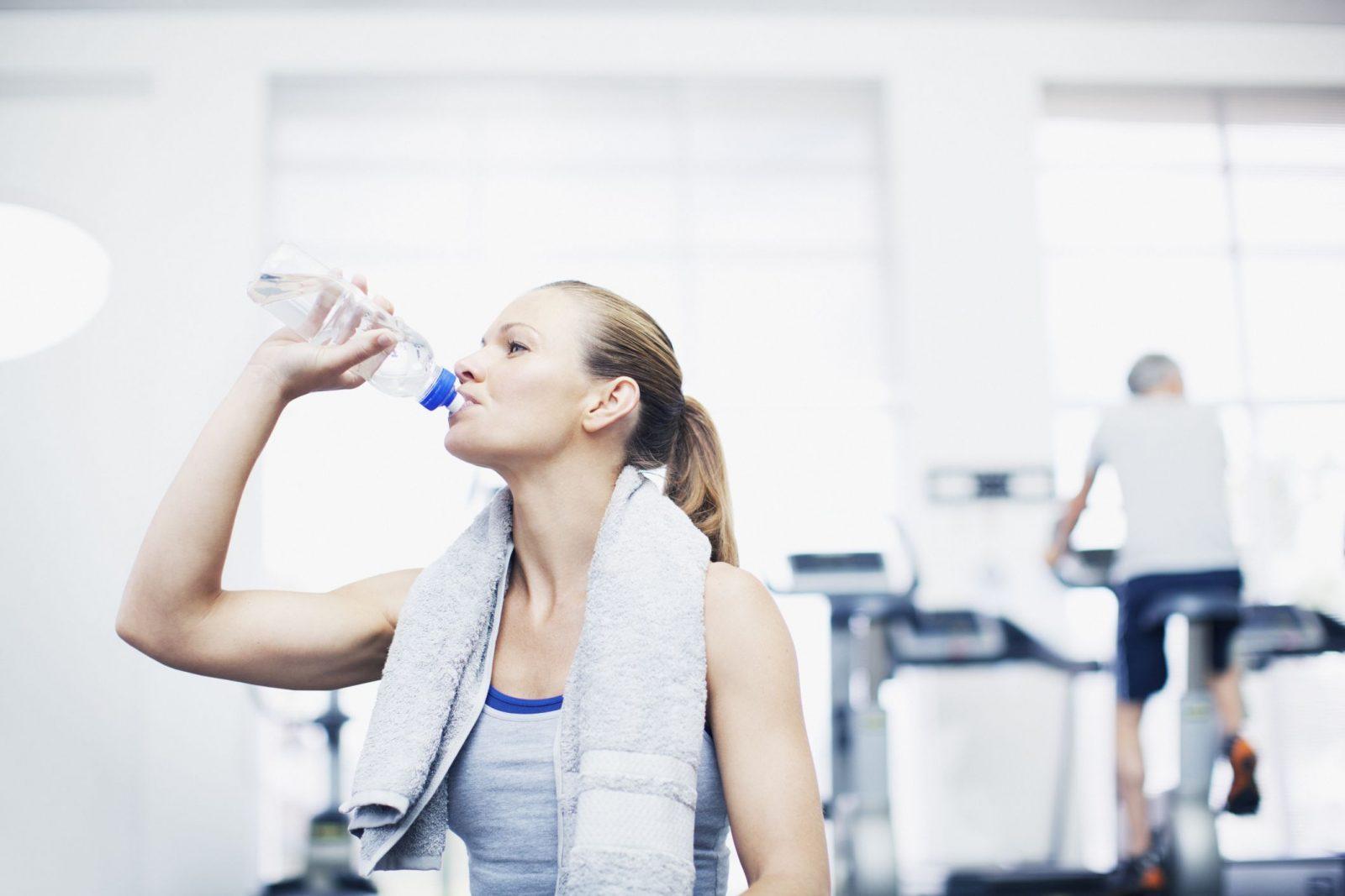 Девушка с полотенцем на шеи пьет воду в тренажерном зале