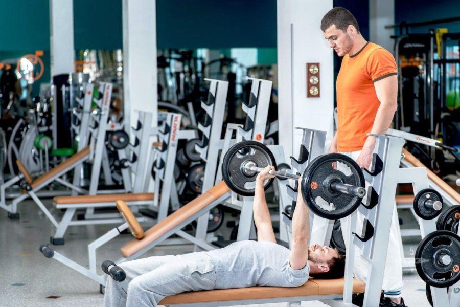 Фитнес инструктор подстраховывает новичка в упражнении жим штанги лежа