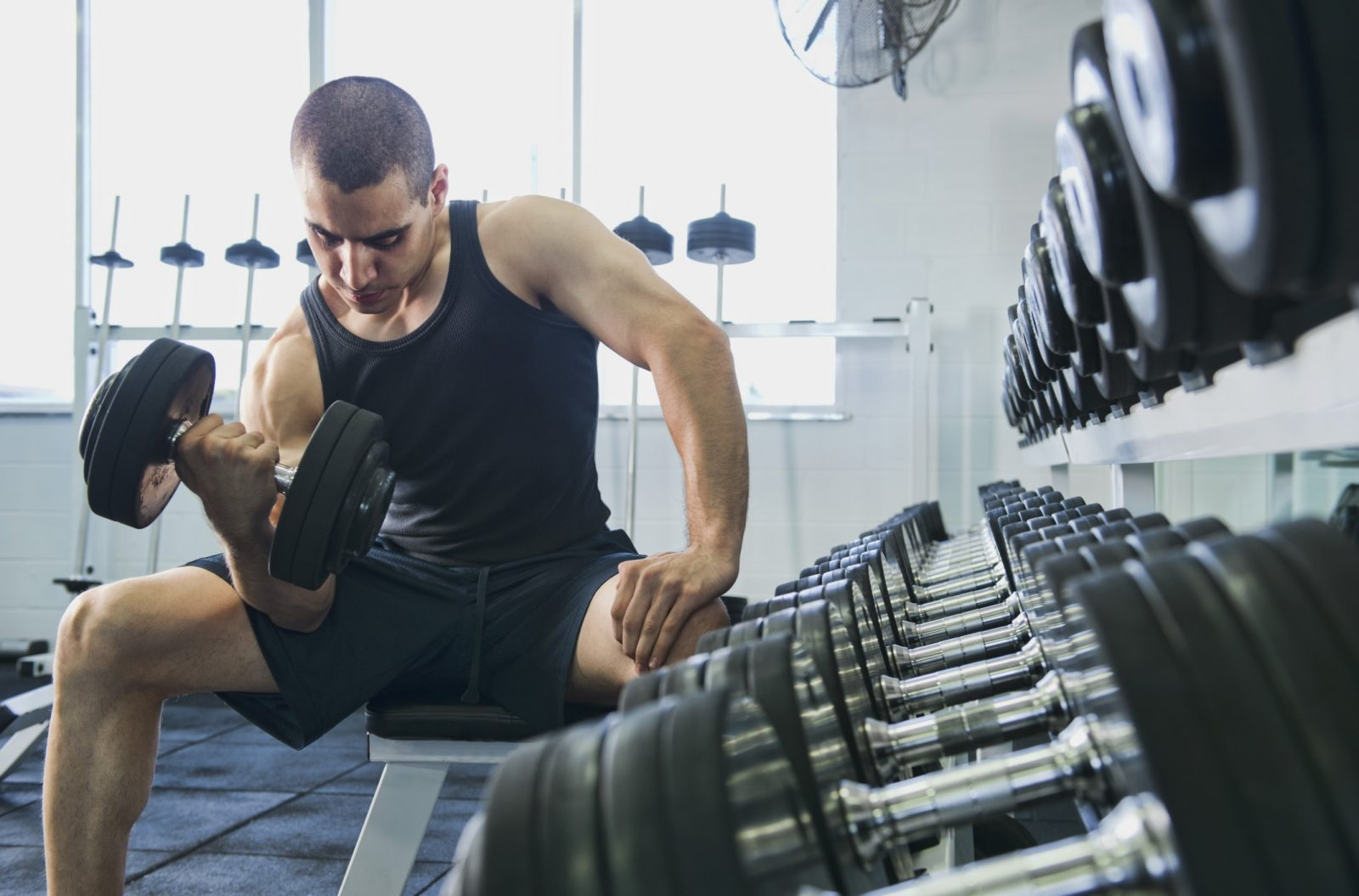 Спортивный парень в тренажерном зале выполняет концентрированный подъем гантели на бицепс