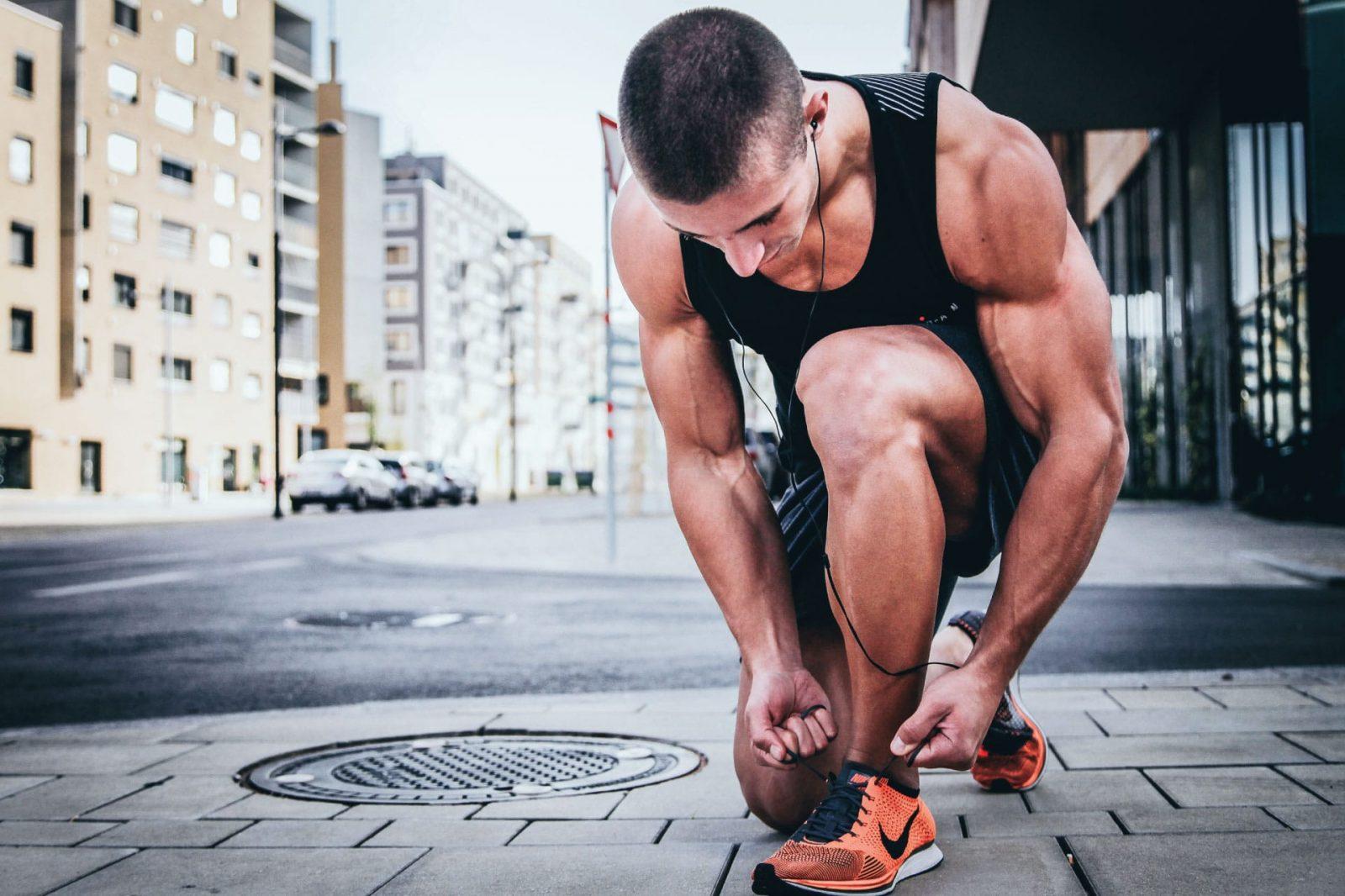 Спортсмен готовится в бегу на улице (завязывает шнурки на кроссовках)