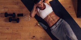Загорелая, спортивная девушка делает скручивания на пресс на коврике