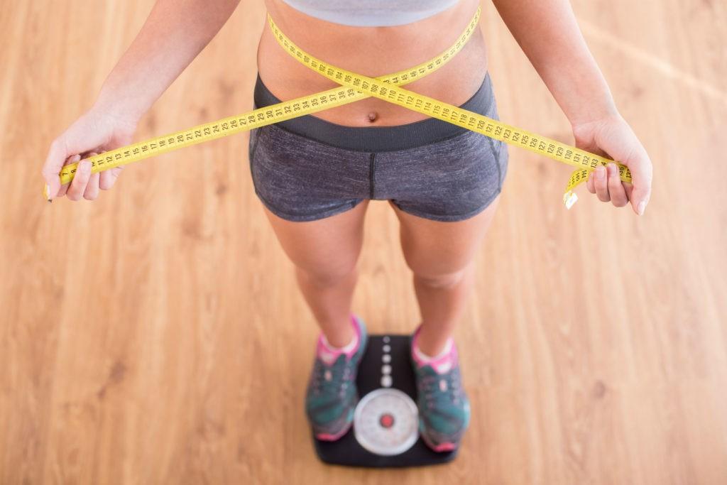 Стройная девушка на напольных весах