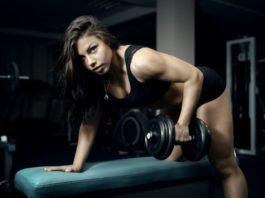 Спортивная девушка в темной одежде выполняет тягу гантели в наклоне в тренажерном зале